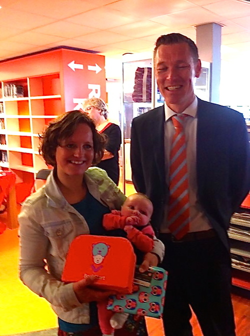 Kersverse moeder en haar baby ontvangen het BoekStartkoffertje van de wethouder